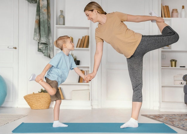 Full shot woman and boy exercising together