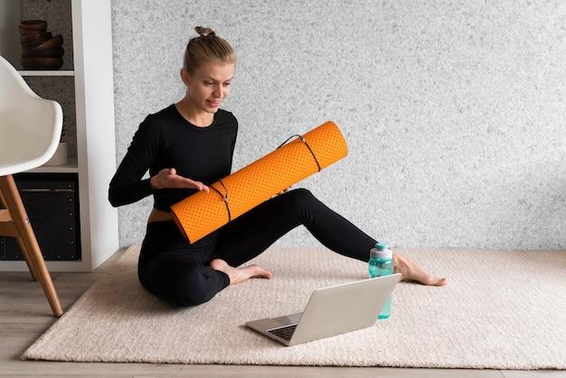 Donna piena del colpo sul tappeto con il computer portatile