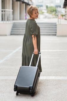 荷物を運ぶフルショットの女性