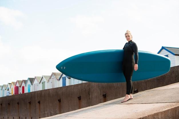Full shot woman carrying paddleboard