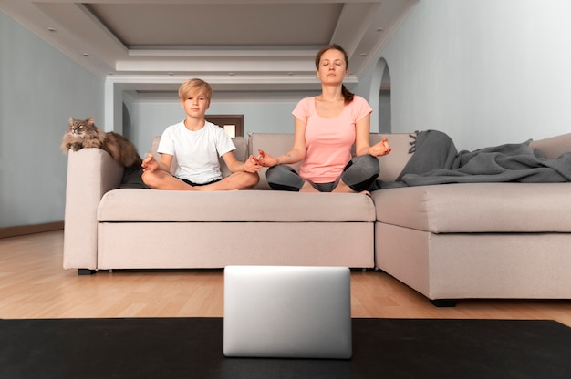 Full shot woman and child meditating