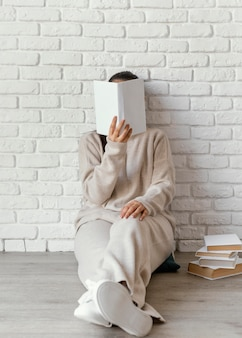 Full shot woman covering face with book