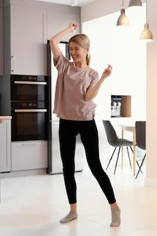 Full shot woman dancing at home