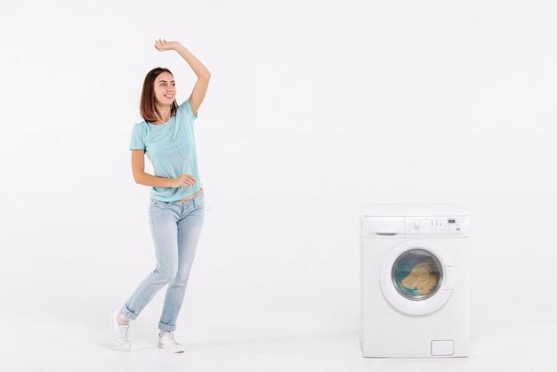 Full shot woman dancing near washing machine