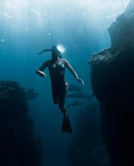 Full shot woman diving with equipment