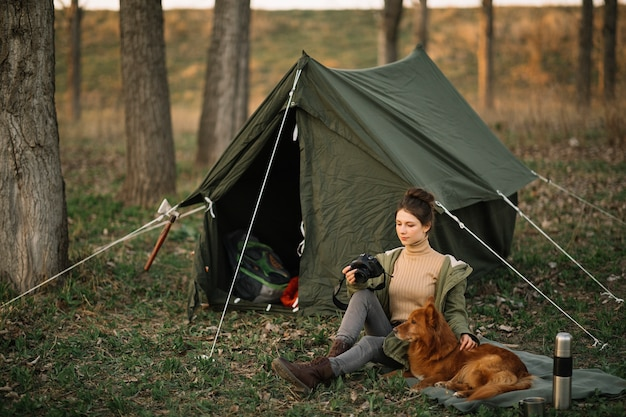 Full shot woman and dog near tent