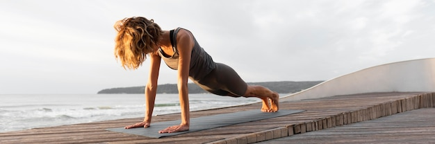 Full shot woman doing plank outside