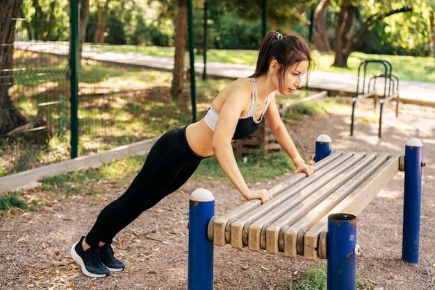 Full shot woman doing pushups outside