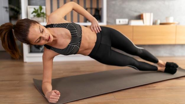 Full shot woman doing side plank