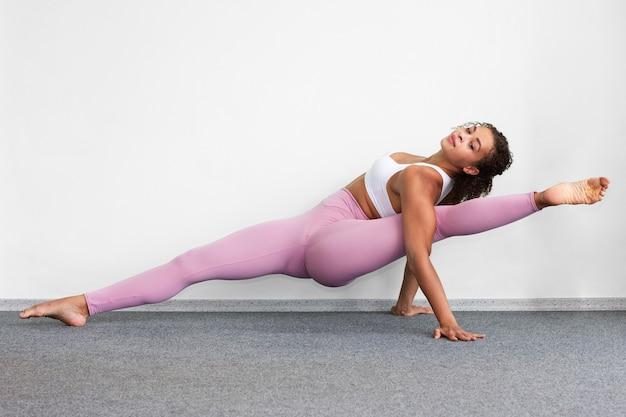 Full shot woman doing the splits indoors