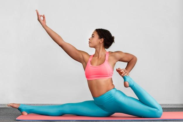 Full shot woman doing the splits on mat