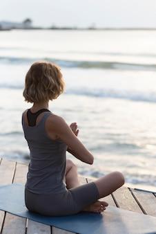 Full shot woman doing sukhasana on mat facing sea