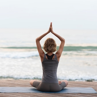 Full shot woman doing sukhasana pose outside facing sea