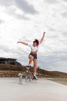 스케이트로 트릭을 하는 전체 샷 여자