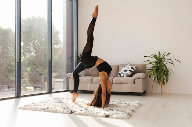 Full shot woman doing yoga at home