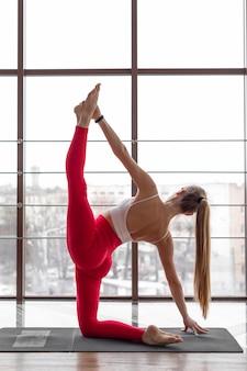 Donna piena del colpo che fa yoga sulla stuoia