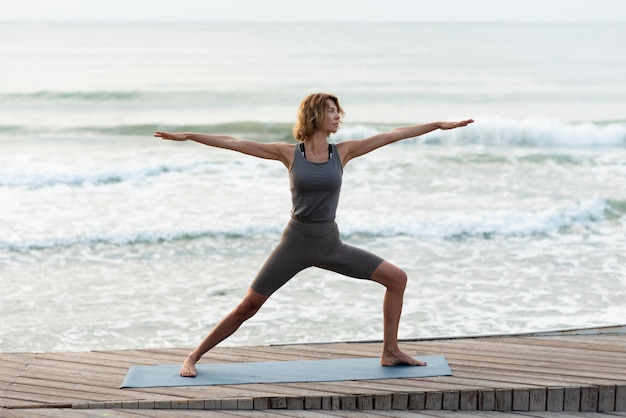 Full shot woman doing yoga pose near sea