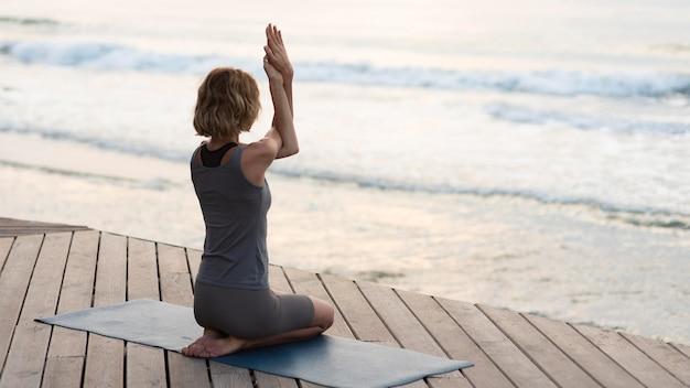 Женщина в полный рост делает позу йоги на коврике снаружи