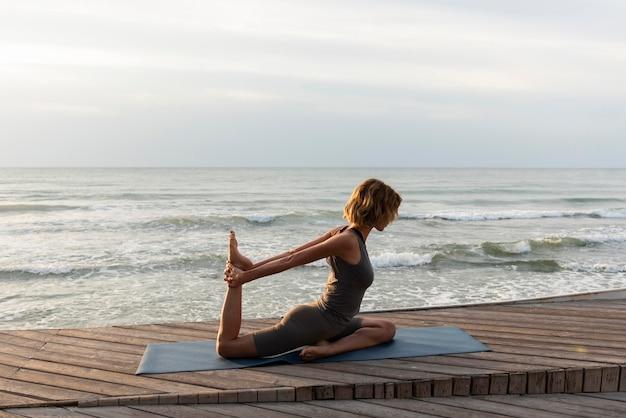 Женщина в полный рост делает позу йоги снаружи на коврике