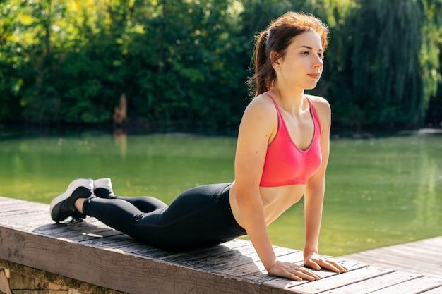 Donna piena del colpo che fa posa di yoga