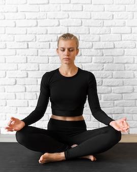 Женщина в полный рост делает позу йоги