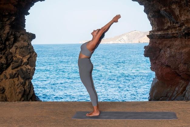 Donna a tutto campo che fa yoga in riva al mare