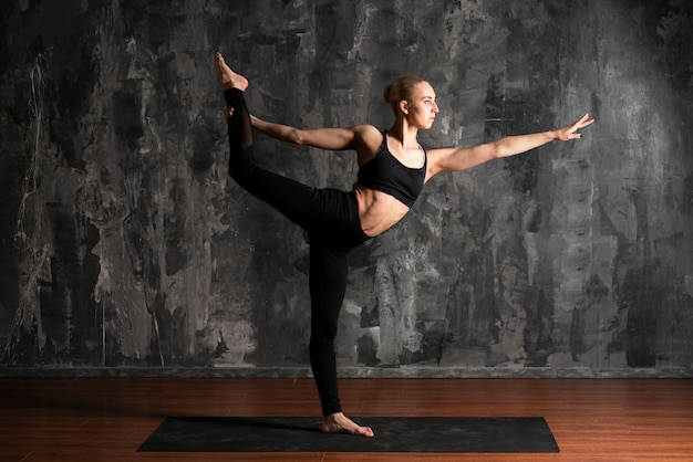 Full shot woman doing yoga with stucco background