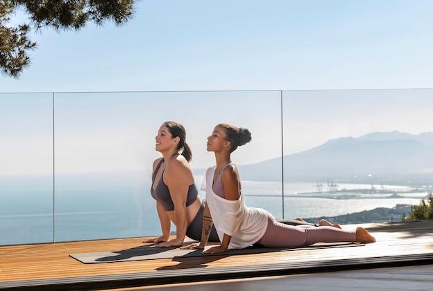 Full shot woman doing yoga with teacher