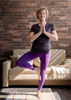 Donna piena del colpo che fa yoga