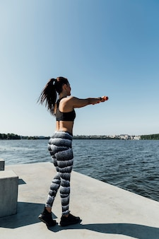 Full shot of woman exercising by the lake