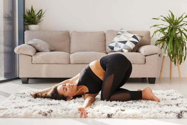 Donna piena del colpo che si esercita sul tappeto