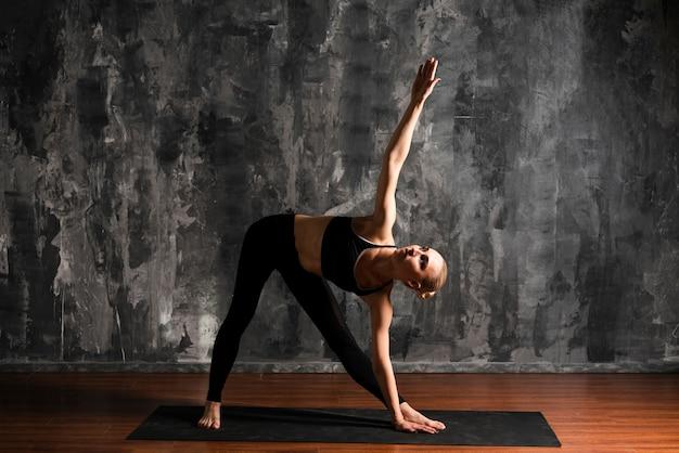 Full shot woman exercising indoors