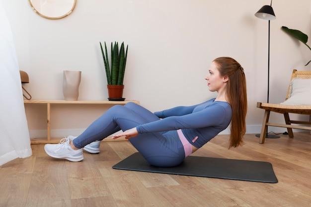 Полный снимок женщины, тренирующейся на коврике дома Бесплатные Фотографии