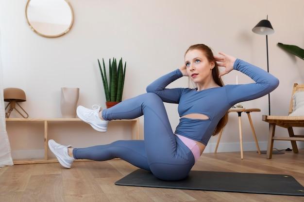 Полный снимок женщины, тренирующейся на коврике в помещении