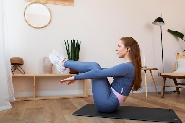 Полный снимок женщины, тренирующейся на коврике внутри