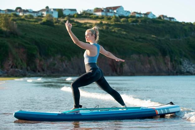 Full shot woman exercising on paddleboard