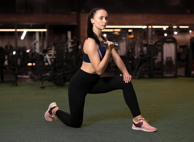 Full shot woman exercising with dumbbell
