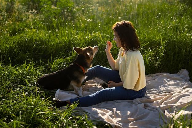 Donna a tutto campo che dà da mangiare al cane in natura