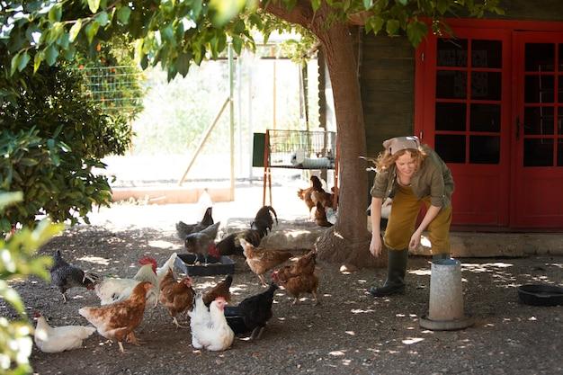 鶏に餌をやるフルショットの女性