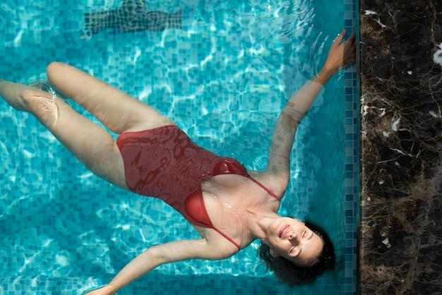Full shot woman floating in pool