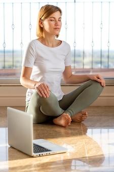 Donna piena del colpo sul pavimento con il computer portatile