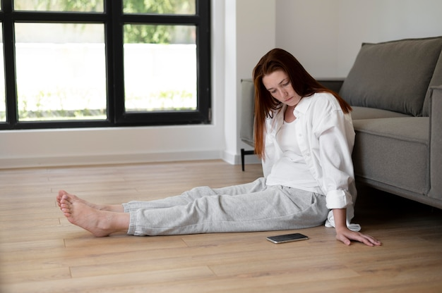 Full shot woman on floor with phone