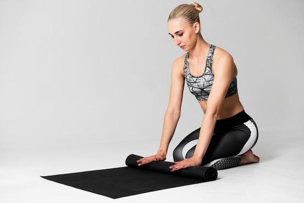 Full shot woman folding yoga mat
