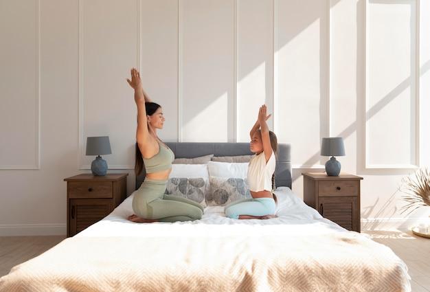 Donna e ragazza a tutto campo che meditano a letto