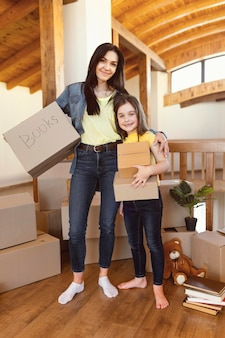 Full shot woman and girl with boxes