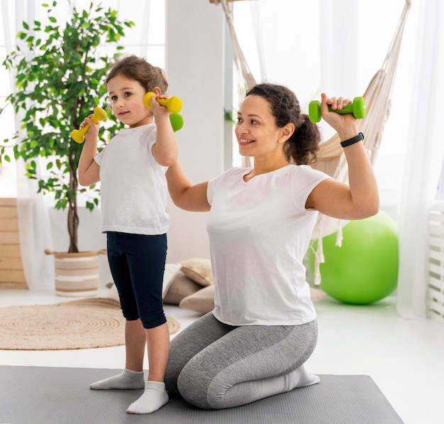 Full shot woman and girl with dumbbells