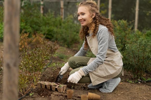 Donna a tutto campo che coltiva piante
