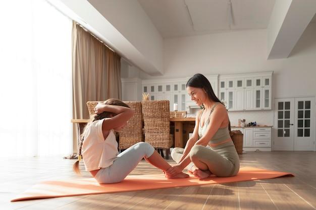 Полный снимок женщина помогает ребенку упражнения