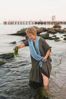 Donna piena del colpo che tiene alghe