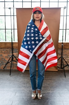 Полный снимок женщины, держащей американский флаг